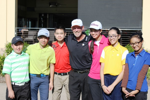 Teaching pro Tony Blacker poses with a group of his young golfing students.